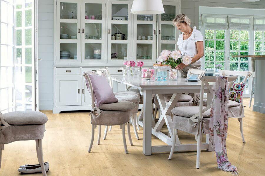 Vrouw zet bloemen op tafel en staat op laminaat